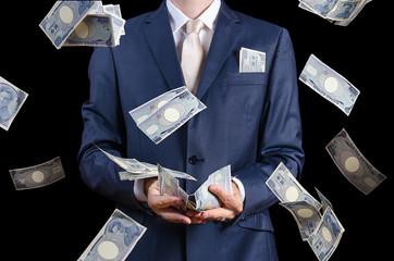 Businessman catching falling money