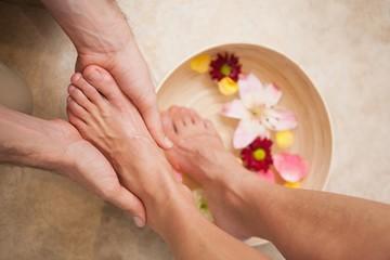 Pedicurist washing a customers feet