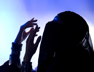 Ramadan: Beautiful young muslim girl praying, Dark silhouette