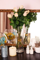 Beautiful vase with roses near mirror