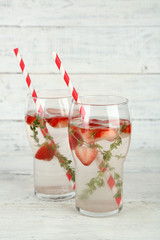 Tasty cool beverage with strawberries and thyme,