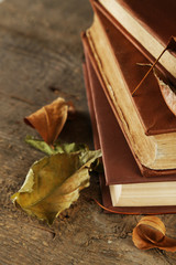 Books and dry leaves on wooden background