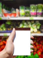 white blank notebook in woman hand and vegetables background