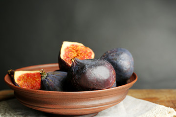 Ripe sweet figs in bowl on wooden table, on dark background