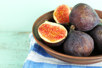 Ripe sweet figs in bowl on wooden background
