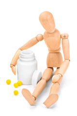 Wooden man embracing medical container with vitamins