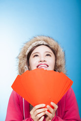 happy asian girl with winter wear and holding red bag for chines