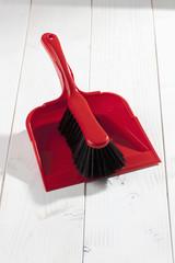 Roter Handfeger und Schaufel auf weissem Holzuntergrund, Studio