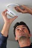 Homme posant un détecteur de fumée