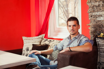 Young man sitting in a cafe or living room