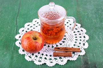 Goji berries drink in glass cup, ripe apple and cinnamon