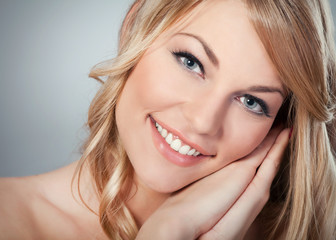 Close-up of a beautiful blond woman with a perfect smile.