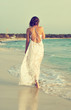 Woman in white dress walking on the beach.