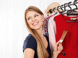 Seasonal sale. Young female customer buying clothes in store