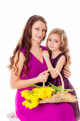 happy mother and daughter with a bouquet of yellow tulips