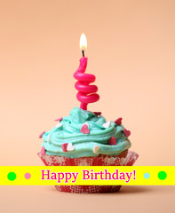Delicious birthday cupcake on table on beige background