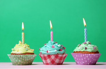 Delicious birthday cupcakes on table on green background