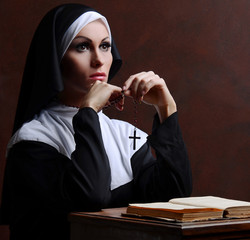 Young attractive nun praying