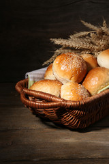 Tasty buns with sesame in wicker basket, on  wooden background