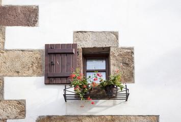 ventana con postigos de madera y geranios  rojos en el exterior