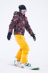 Young girl snowboarder in yellow pants on the board