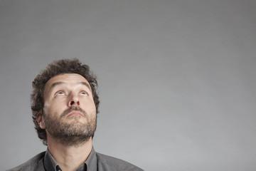 Mann in grauem Hemd schaut nach oben