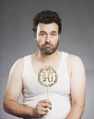 Mann mittleren Alters, mit Vollbart, im Unterhemd