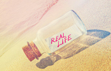 "Message in a bottle ""Real life"" on sandy beach."