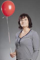 Frau mitttleren Alters hält roten Ballon