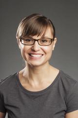 Braunhaarige Frau vor grauem Hintergrund, lachend, Portrait.