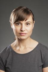 Braunhaarige Frau vor grauem Hintergrund, Portrait.