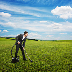 smiley businessman vacuuming green grass