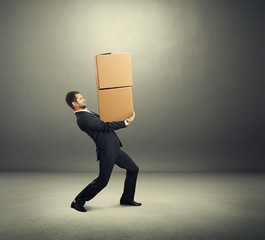 tired businessman carrying two boxes