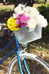 Bicycle with flowers in metal basket closeup