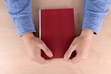 Men reading book on wooden table background