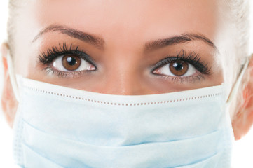 Closeup of the eyes of dentist assistant wearing mask.