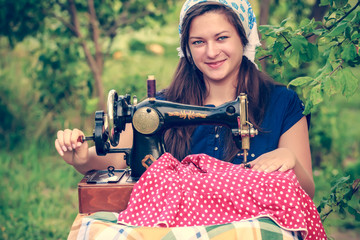 Young woman with vintage hand sewing machine