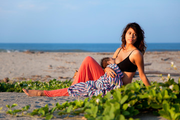 Beautiful woman breastfeeding at the beach