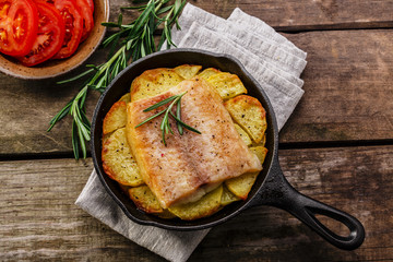 Baked fish fillets with potatoes in a frying pan