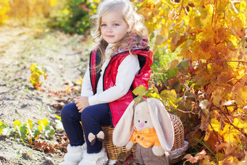 Little girl in warm clothes with toy rabbit