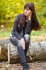 Girl sitting on a felled tree