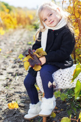 Adorable little girl in warm clothes, autumn time