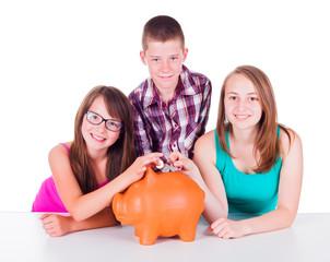 Teenage putting coins into big piggy bank