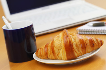 Butter croissant and black coffee on office desk