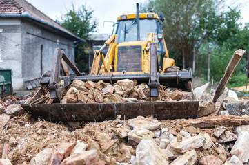 bulldozer demolishing an old building and carrying debris