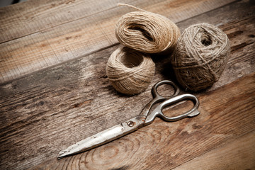 Old scissors and skein jute on wooden table