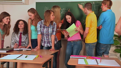Group student near green blackboard in classroom.