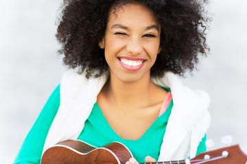 Afro woman playing ukulele