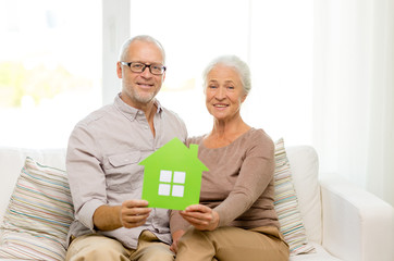 happy senior couple hugging on sofa at home