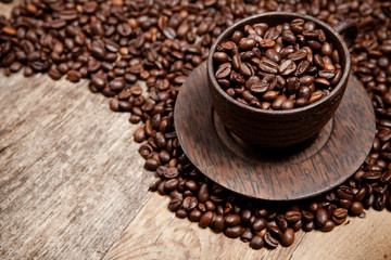 Coffee cup with coffee beans on wooden table